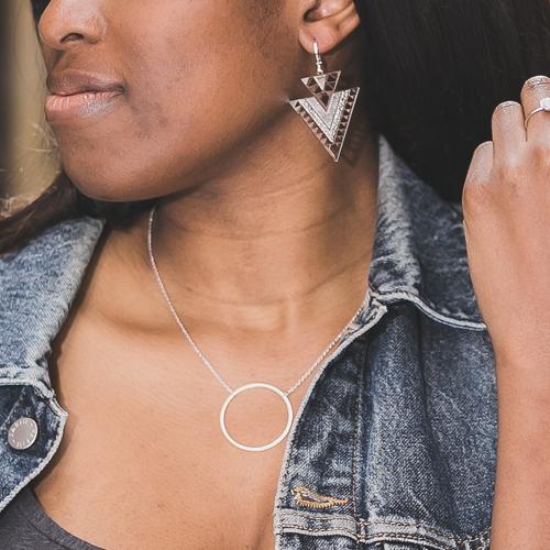 boucle d'oreille plaqué argent arrow en forme de triangle et collier en forme de rond portée par une femme