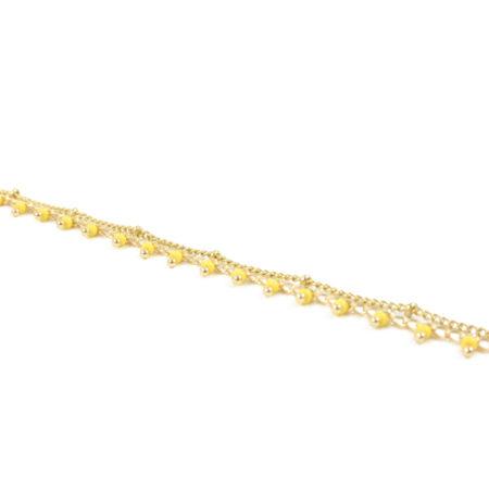 bracelet en acier inoxydable doré avec des rocaille jaune sur fond blanc