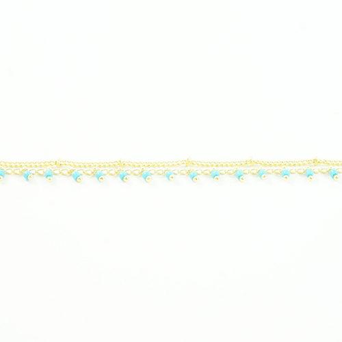 bracelet en acier inoxydable doré avec des rocaille bleu ciel sur fond blanc