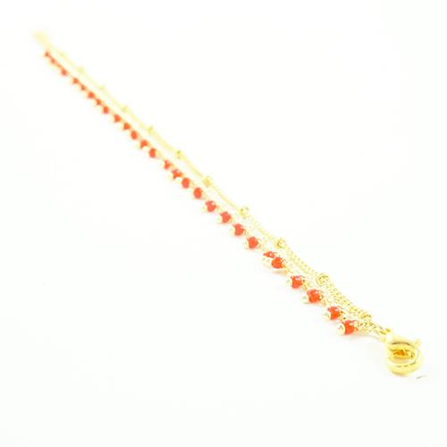 bracelet en acier inoxydable doré avec des rocaille rouge sur fond blanc
