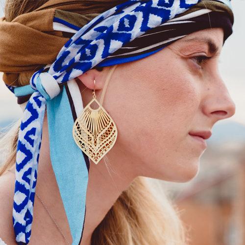 boucle d'oreille plaqué or Ela en forme de feuille porté par une femme