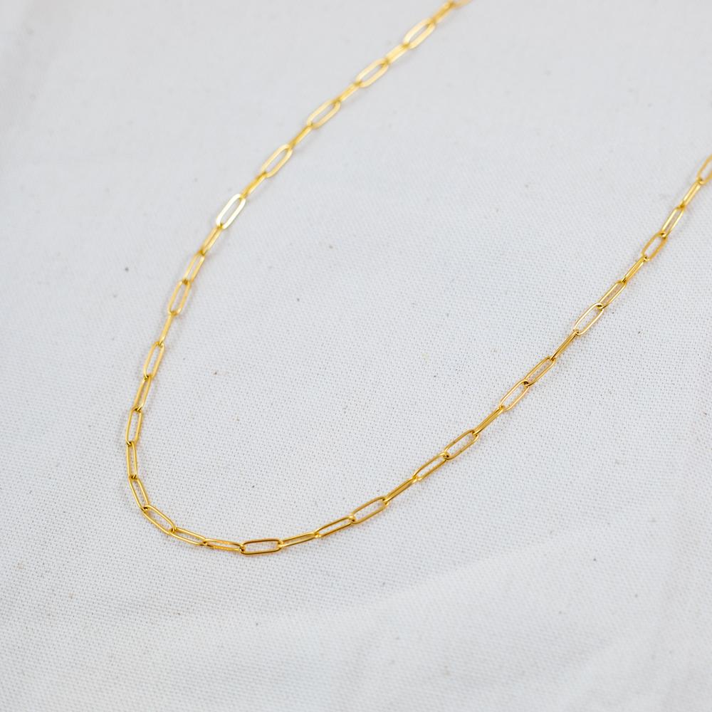 collier plaqué or trombone sur fond blanc