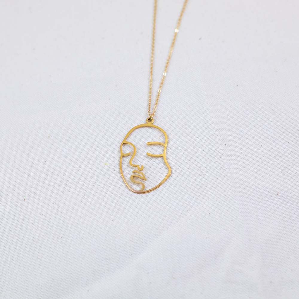 collier plaqué or viviane en forme de visage sur fond blanc