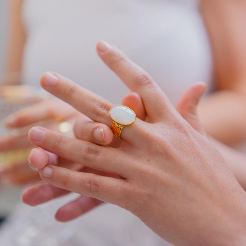 bague plaqué or ovide pierre blanche porter par une main