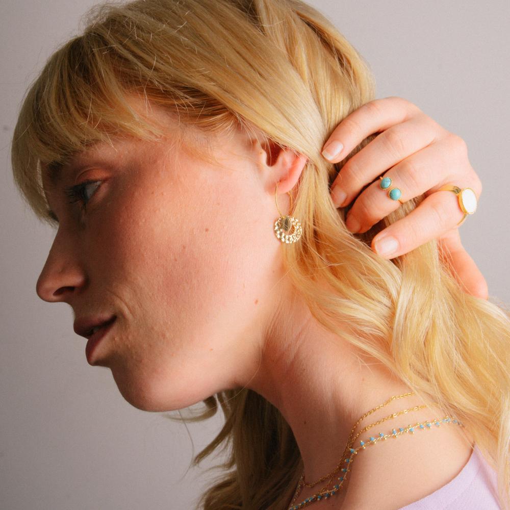 boucle d'oreille acier inoxydable doré mariel en forme de rond portée par une femme