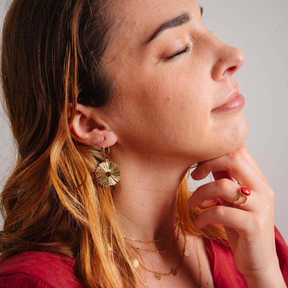 boucles d'oreilles créoles plaqué or en forme de fleur porter par une femme