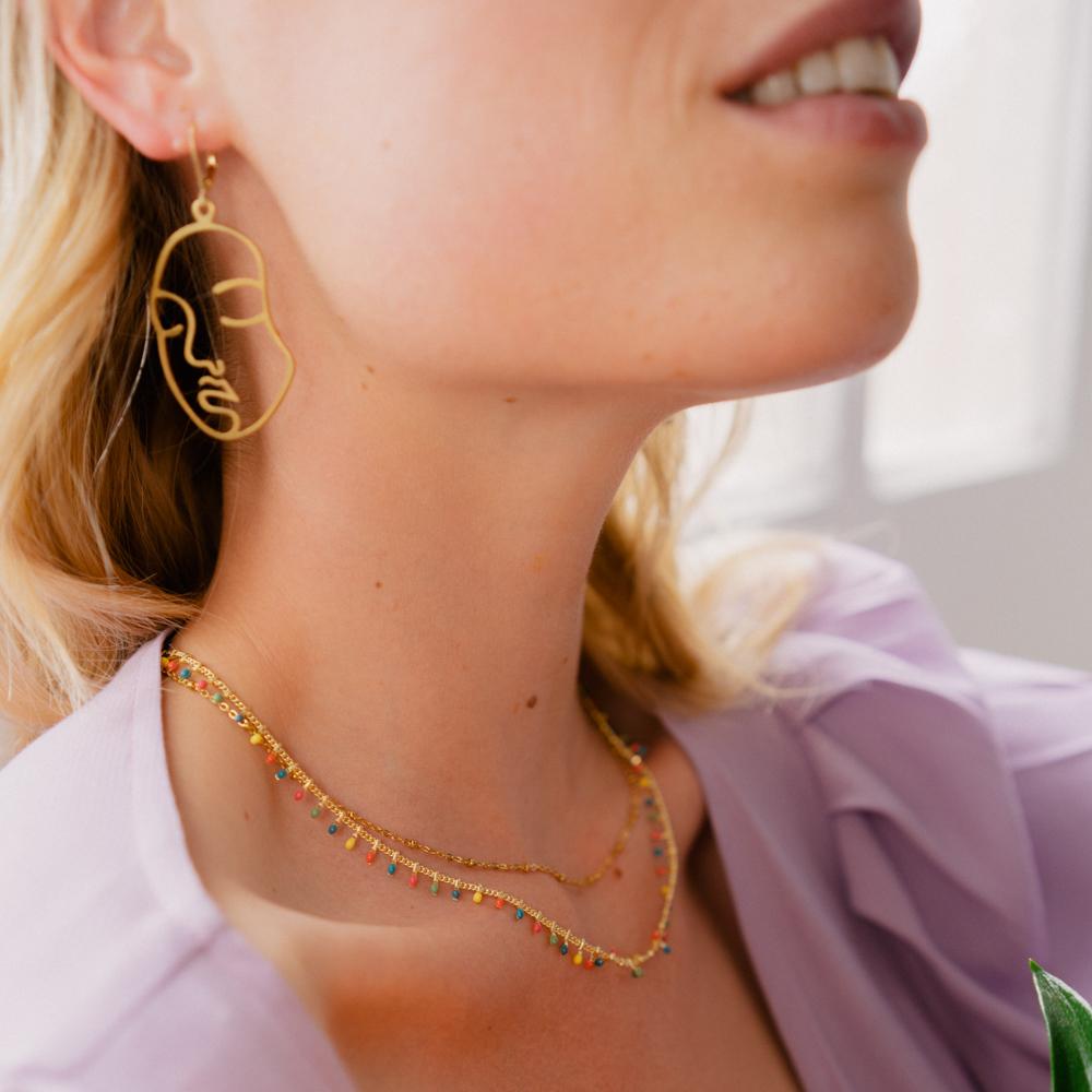 boucle d'oreille plaqué or viviane en forme de visage portée par une femme