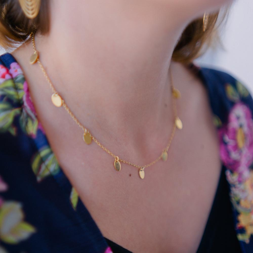 collier plaqué or meg en forme de guirlande de médaillons portée par une femme